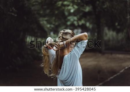 beautiful girl with long hair braids hair spike. beautiful girl braids hair before surfing - stock photo