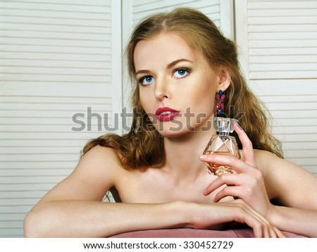 Beautiful girl with long hair holds perfume - stock photo