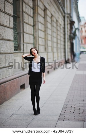 beautiful girl with long hair in a white shirt and a black cardigan and black mini-skirt and black pantyhose walking down the street and straightens hair - stock photo
