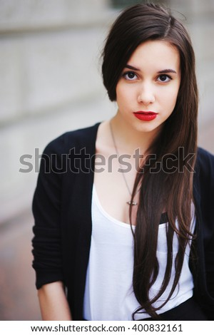 beautiful girl with long hair in a white shirt and a black cardigan looking with painted red lipstick lips
