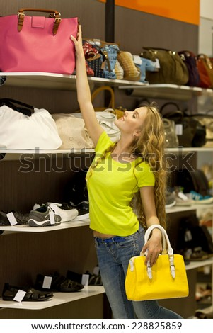 Beautiful girl with long hair in the store chooses bags