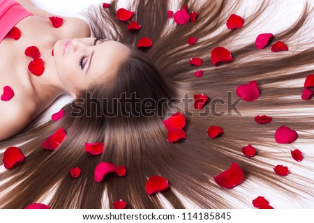 beautiful girl with long hair lying on white - stock photo