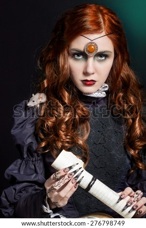 beautiful girl with long hair mode in the image of the witch with the mouse on his shoulder, black long false nails with bright makeup - stock photo