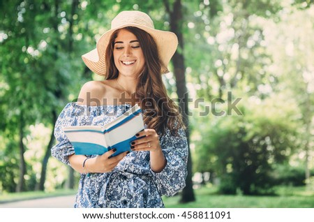 Beautiful girl with long hair sitting on bench  read book in park outdoors .