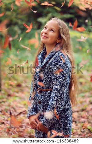 Beautiful girl with long hair standing in the autumn park and looking at yellow leaves. - stock photo