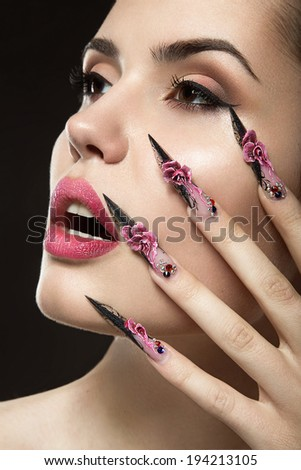 Beautiful girl with long nails and sensual lips. Portrait shot in the studio on a black background.