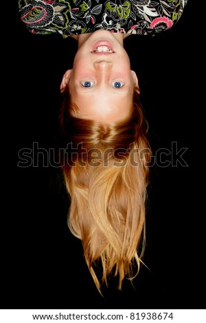 Beautiful girl with long red hair hanging upside down - stock photo