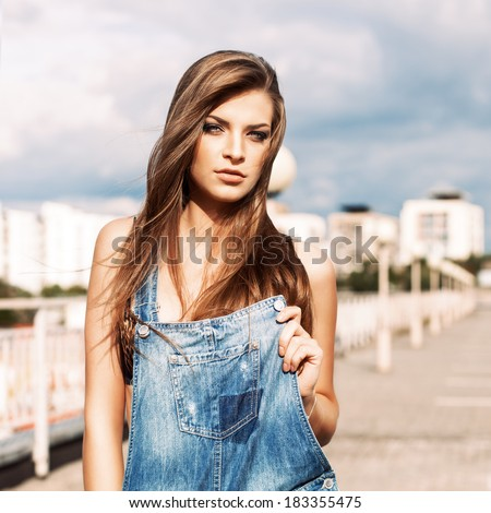beautiful girl with long silky hair in denim short overalls holding front part of it - stock photo