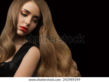 Beautiful girl with long thick shiny hair on a black background. Curly brown hair. Red lipstick