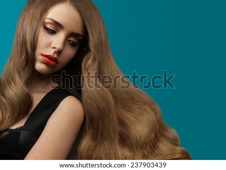 Beautiful girl with long thick shiny hair on a blue background. Curly brown hair. Red lipstick - stock photo
