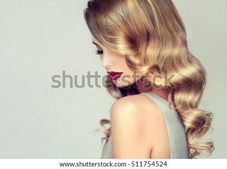 Beautiful girl with long wavy hair .  Blonde with curly hairstyle and red lips