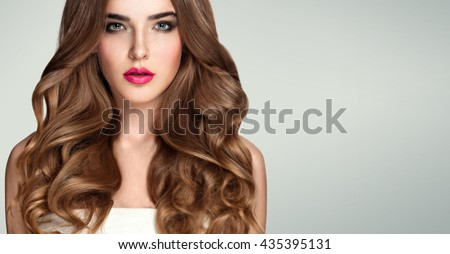 Beautiful girl with long wavy hair . Blonde with curly hairstyle. Sensual lips, sexy expressive eyes, gray background. Closeup portrait of young  blond woman. - stock photo