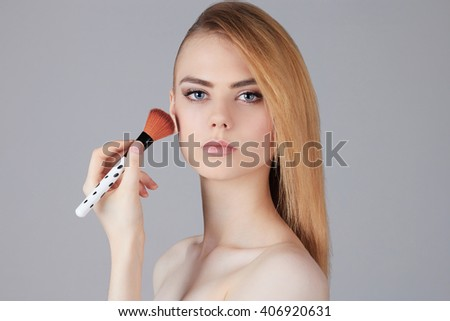 beautiful girl with make-up brush.beauty woman Applying Make-up.clean skin cosmetics.Young woman face with perfect skin - stock photo