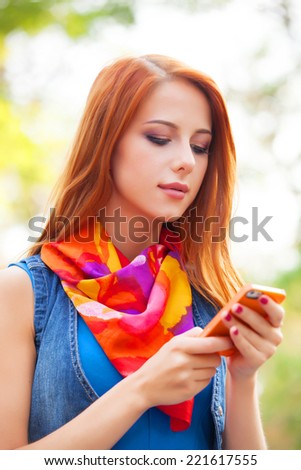 Beautiful girl with mobile phone in the park.