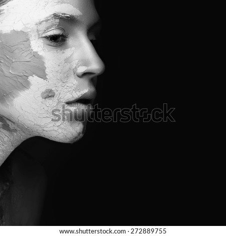 Beautiful girl with mud on his face. Cosmetic mask. Beauty face. Picture taken in the studio on a black background. Black&white photo