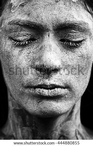 Beautiful girl with mud on his face. Cosmetic mask. Beauty face. Picture taken in the studio on a black background. Black&white photo. - stock photo