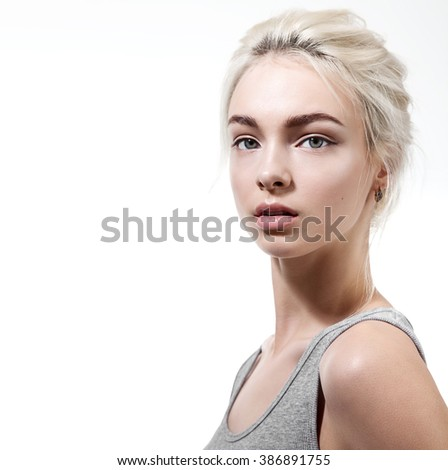 Beautiful girl with natural make-up in a gray shirt on a white background - stock photo