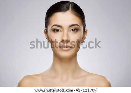 Beautiful girl with nice make-up and ponytail looking at camera. Beauty portrait, full face, head and shoulders. Indoor, studio, gray background - stock photo