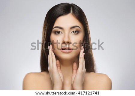 Beautiful girl with nice make-up looking at camera and touching her face by hands. Beauty portrait, head and shoulders. Indoor, studio, gray background