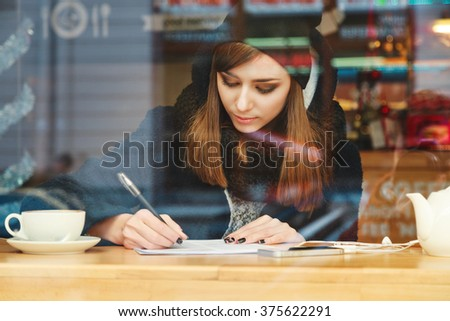 Beautiful girl with nude make up and brown hair wearing black coat and black scarf, writing in notebook and sitting with cup of coffee behind huge window. - stock photo