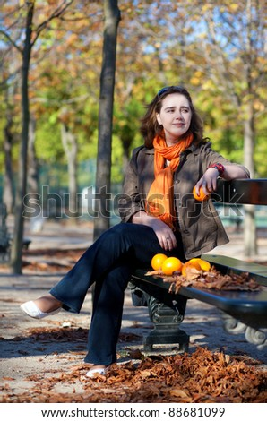 Beautiful girl with oranges sitting at the bench in Paris by fall