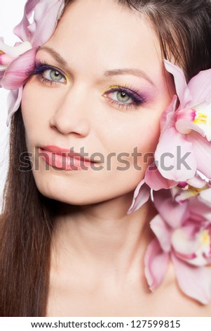 Beautiful girl with orchid flower in hair