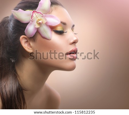 Beautiful Girl with Orchid Flower. Pastel Colors. Perfect Face Skin.Beauty Portrait. - stock photo
