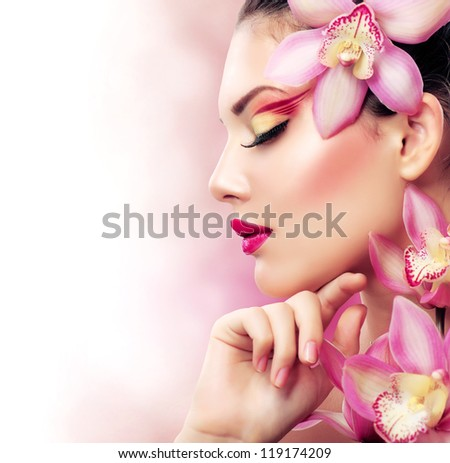 Beautiful Girl With Orchid Flowers.Beauty Model Woman Face. Perfect Skin. Professional Make-up.Makeup.Isolated on a White Background. Fashion Art - stock photo