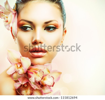 Beautiful Girl With Orchid Flowers.Beauty Woman Face.Vogue Styled Fashion Portrait. Professional Make-up.Makeup