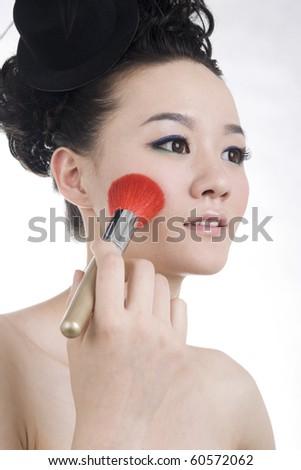 Beautiful girl with perfect makeup,makeup brush on face - stock photo