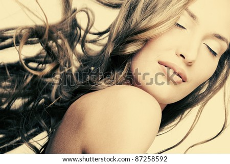 beautiful girl with perfect skin and long flowing hair on a yellow background, sepia - stock photo