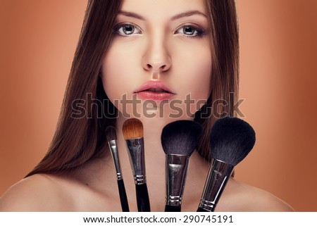 Beautiful girl with perfect skin and make up brushes. Studio shooting. Beauty and fashion. Sensuality. Healthy skin and make up - stock photo