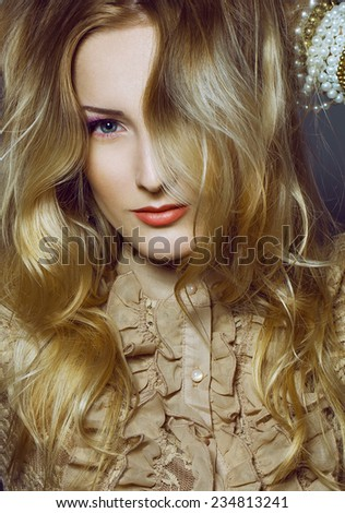beautiful girl with perfect skin, blond hair and blue eyes posing on the gray background.  - stock photo