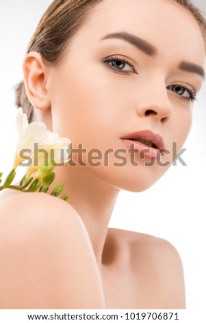 beautiful girl with perfect skin holding flower, isolated on white
