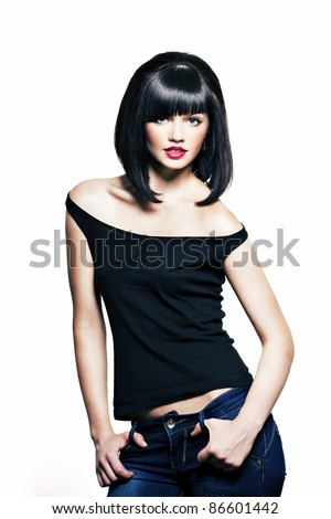 beautiful girl with perfect skin in a black shirt and jeans with black short hair and bright red lipstick - stock photo