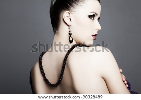 beautiful girl with perfect skin in black dress with jewelry on a dark background - stock photo