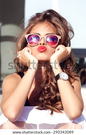 Beautiful girl with perfect teeth and tan skin and pink lips wearing the jewelry bracelet with the stones wear summer outfit,send kiss closing her eyes and smiling cause the last summer sunrise - stock photo