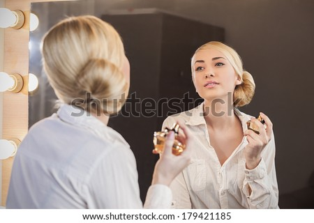 Beautiful girl with perfume looking at the mirror  - stock photo