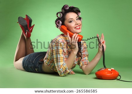 beautiful girl with phone, pin-up girl . studio photography on green background, stylish hairstyle and make-up, bright emotions - stock photo