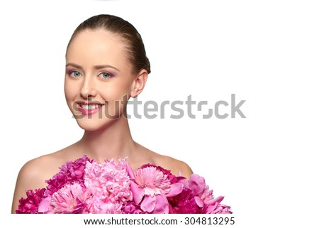 Beautiful girl with pink peony flowers. Closeup of beauty model woman with perfect skin and professional makeup looking smiling at the camera - stock photo