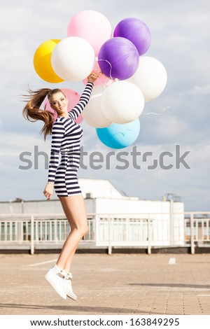 beautiful girl with ponytail hair in short black and white striped dress and white high sneakers jumps holding bunch of multicolored balloons - stock photo