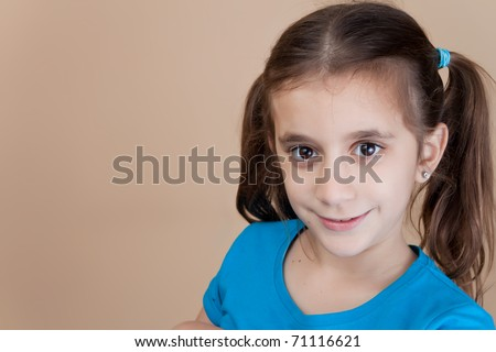 Beautiful girl with ponytails wearing a blue shirt and smiling at the camera - stock photo