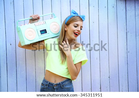Beautiful girl with pretty smile holding retro tape recorder on color wooden background - stock photo
