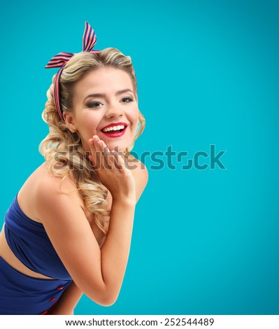 Beautiful girl with pretty smile in pinup style on blue background - stock photo