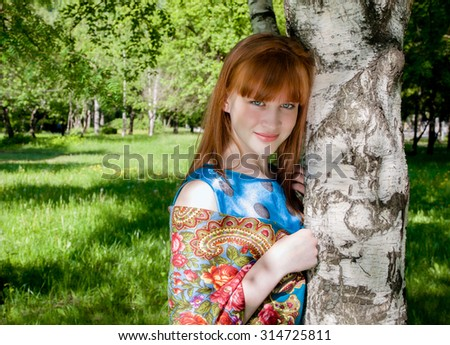 Beautiful girl with red hair in  headscarf with bright patterns on the shoulders - stock photo