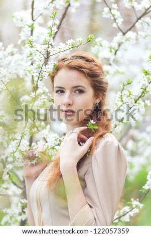 beautiful girl with red hair in spring cherry garden - stock photo