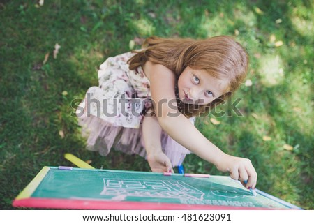 Beautiful girl with red hair preparing for school and writing on blackboard in nature.