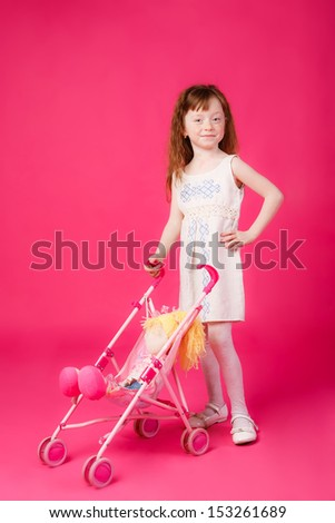 beautiful girl with red hair with a toy stroller. mimics mom - stock photo