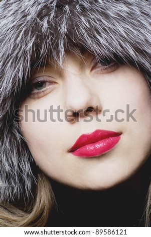 Beautiful girl with red lips in fur hat