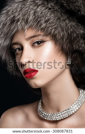 Beautiful girl with red lips in fur hat. Black background in studio - stock photo